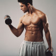 Hispanic young man doing heavy dumbbell exercise — Stock Photo #49225427