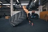 Fit female athlete flipping a huge tire — Stock Photo