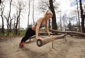 Fit young lady exercising in park — Stock Photo