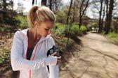 Female runner monitor her progress on smartphone — Stock Photo