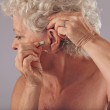 Постер, плакат: Mature woman inserting a hearing aid in her ear