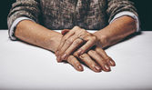 Senior woman's hands clasped on a table — Stock Photo