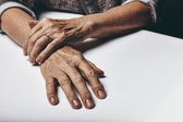 Old female hands on a table — Stock Photo