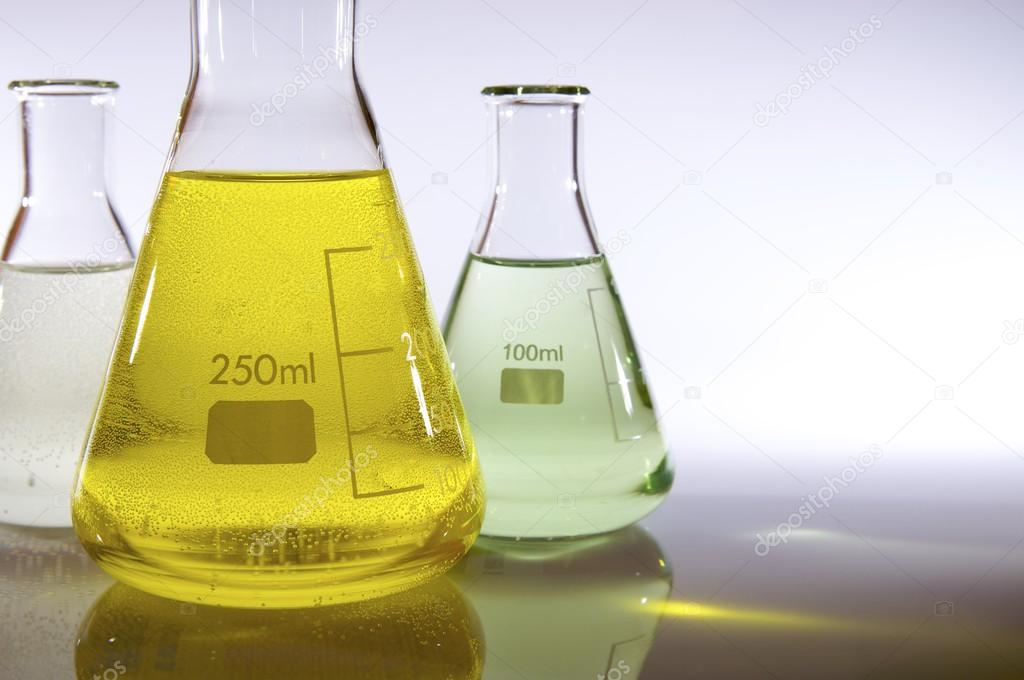 Three graduate laboratory flasks with liquid — Stock Photo #12741294