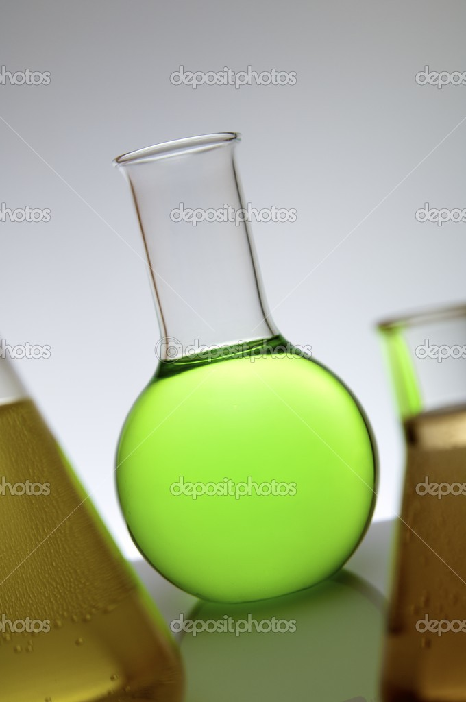 Laboratory flask containing green liquid on a white back-light — Stock Photo #12741469