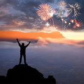 A man at mountain and fireworks — Stock Photo