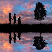 Happy family walking on the lake coast — Stock Photo