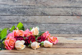 Roses on old wooden table — Stock Photo