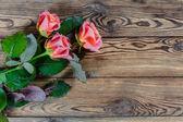 Rosor på rustika bord — Stockfoto