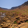 Stream flowing through arid hills — Stock Photo #12381998