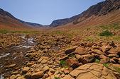 Stream flowing through arid hills — Stock Photo