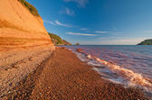 Red Waves on a Red Sandstone Beach — Stock Photo