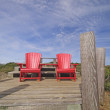 Постер, плакат: Red chairs on a mountain top lookout