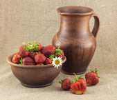 Rustic still life of strawberries in the clay pot — Stock Photo
