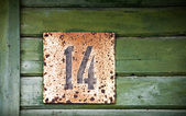 Wooden wall with grunge house number — Stock Photo