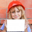 Royalty-Free Stock Photo: Little girl with helmet of construction worker and white blank card