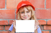 Little girl with helmet of construction worker and white blank card — Stock Photo