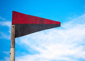 Wooden triangle red-black flag on a playground — Stok fotoğraf