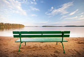 Green wooden bench in front of the lake coast — Stock Photo