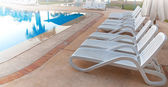 Swimming pool and empty resting chairs — Stock Photo