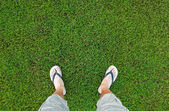 Feet of the man standing on fresh green grass — Stock Photo