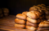 Freshly baked warm traditional Russian pies on wooden counter in bakery — Foto de Stock