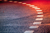 Turning asphalt road with marking lines and bright red reflections — Stock Photo