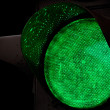 Green traffic light closeup photo above black background — Stock Photo