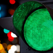 Green traffic light with colorful unfocused lights — Stock Photo #14048679