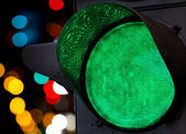 Green traffic light with colorful unfocused lights — Stock Photo