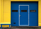 Texture of yellow garage wall with closed blue gate — Stock Photo
