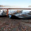 Four small metal rowboats on still foggy lake coast — Stock Photo