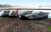 Cuatro pequeños botes metales en la costa del lago brumoso todavía — Foto de Stock