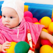Stock Photo: Little baby girl plays with colorful balls