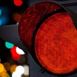 Red traffic light with colorful unfocused lights on a background — Stock Photo