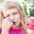Little girl eats big fruit ice-cream in the park — Stock Photo #15681633