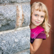 Little blond girl looks out from behind the gray stone wall and smiles — Stock Photo