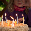 Colorful candles on birthday cake in the dark — Stock Photo #15730375