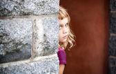 Küçük sarışın kız gri taş duvarın arkasından bakıyor — Stok fotoğraf