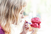 Little girl eats big ice-cream in the park. Profile portrait — Stock Photo
