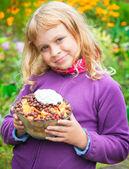 Little blond girl smiles and holds homemade fruit dessert — Stock Photo