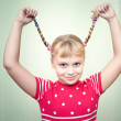 Portrait of smiling little blond girl with two funny pigtails — Stock Photo