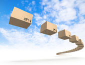 Stream of flying cardboard boxes above blue sk — Stock Photo