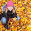 Little blond girl seat on the park ground with yellow autumn leaves — Stock Photo