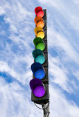 Seven-color rainbow scheme traffic light concept above blue sky — Stok fotoğraf