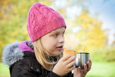 Little beautiful blond girl eating cake with tea in autumnal park — Stock Photo