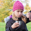 Royalty-Free Stock Photo: Little beautiful blond girl drinks tea and showing thumbs down