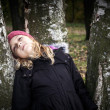Little beautiful blond girl dreamily leaning on the birch — Stock Photo