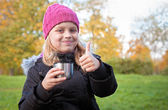 Little beautiful blond girl drinks tea in autumnal park and showing thumbs up — Stock Photo