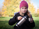 Little beautiful blond girl pours tea from a thermos in park — Stock Photo
